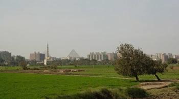 Египетская пирамида на фону городских домов и мечети. Egipt piramid view from Baldeem Ru